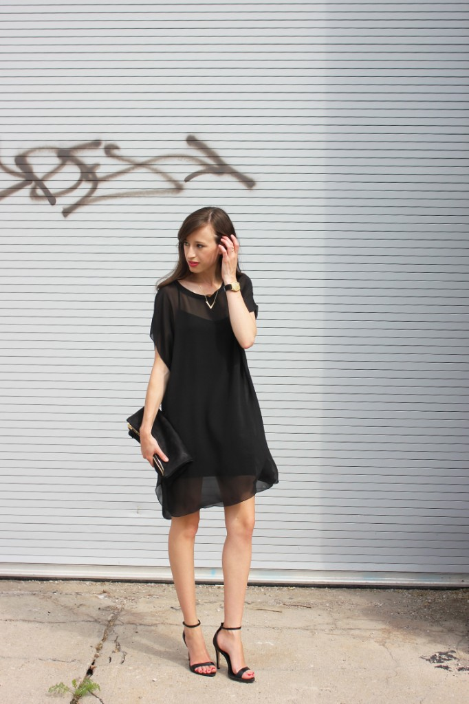 Style Bee in a black sheer dress, black sandals and a black clutch.