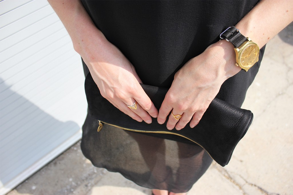 Style Bee in a black sheer dress with a black clutch.