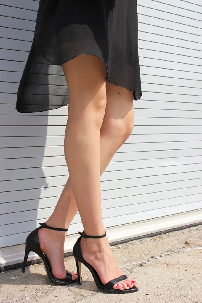 Style Bee in a black sheer dress & black sandals.