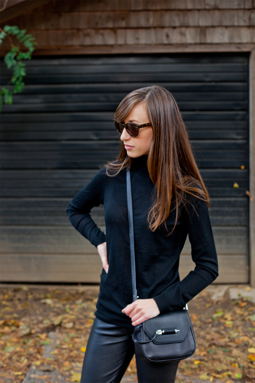 Style Bee in a black turtleneck and Mackage bag.