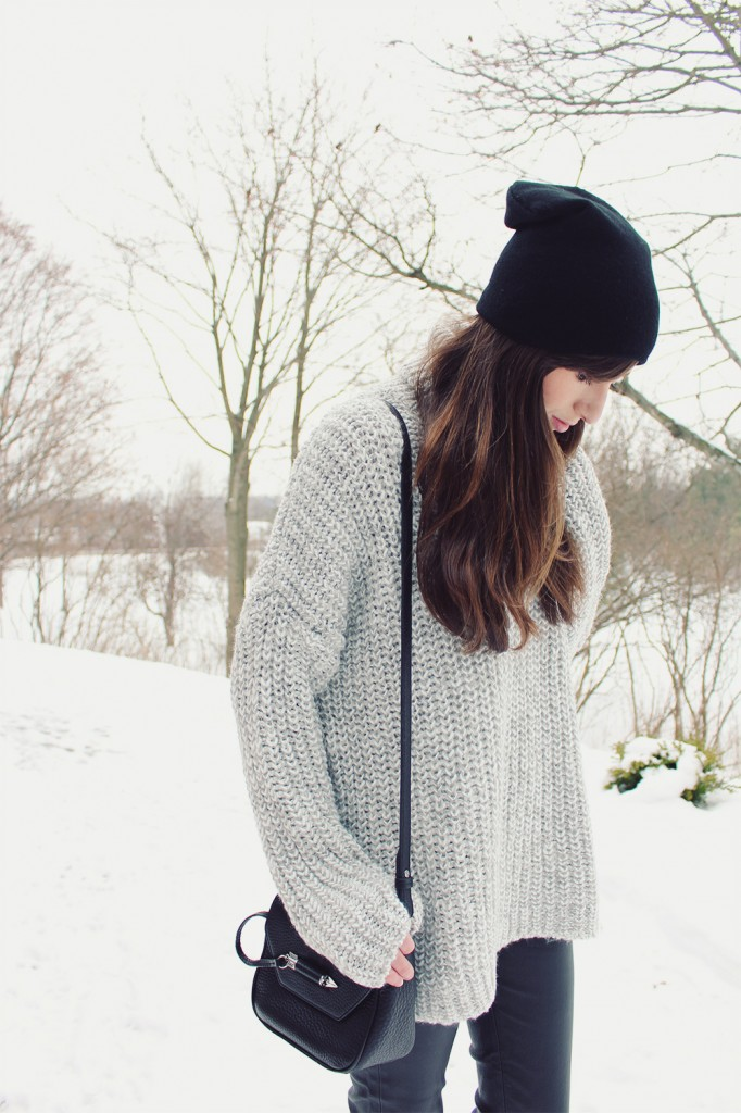 Style Bee in a grey sweater and leather pants.